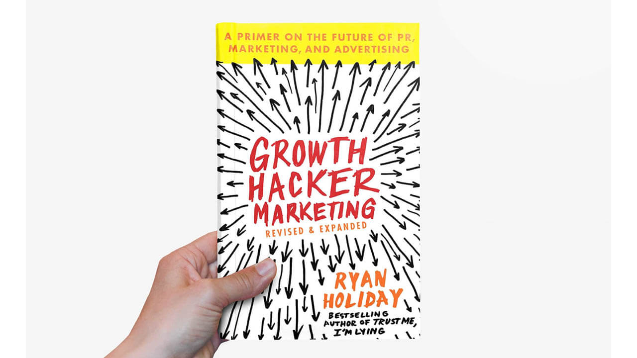 Image of a hand holding a copy of Growth Hacker Marketing